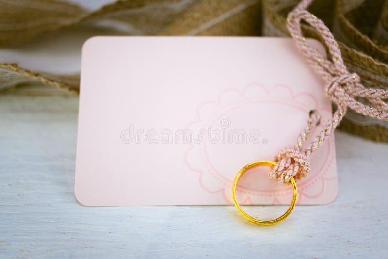 空白的桃红色纸牌和金戒指在白色木背景为 免版税库存图片