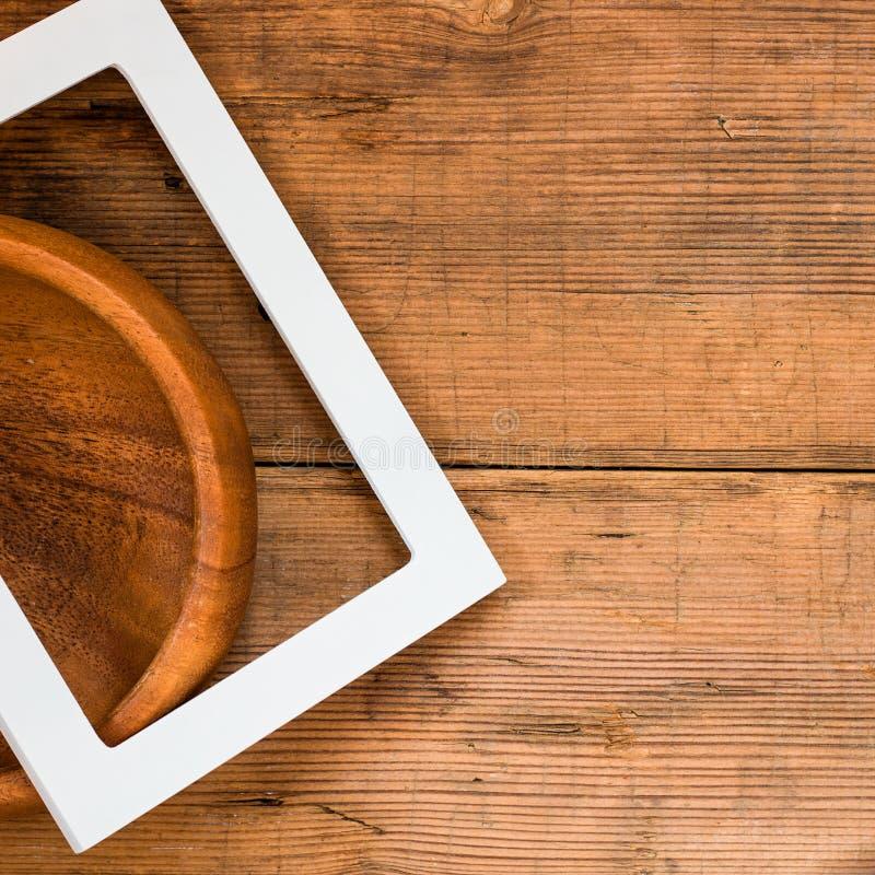 空白的框架和空的碗在棕色木背景纹理 免版税图库摄影