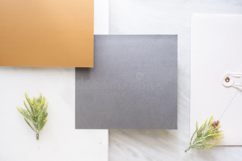 空白的灰色卡片交叠包围和与杉木叶子的金卡片顶视图在两层数步大理石台式 r 免版税库存照片