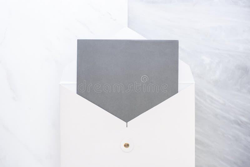 空白的灰色卡片顶视图在白色的包围在两层数步大理石台式 设计显示的假装模板  ?? 免版税库存图片