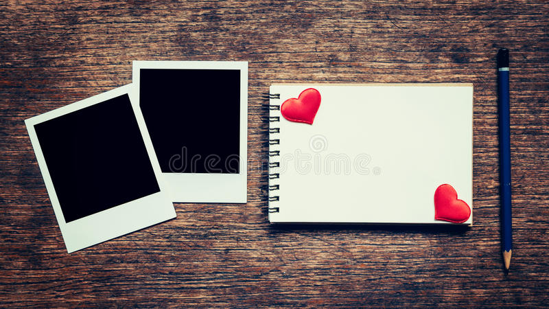 空白的照片框架、笔记本、铅笔和红色心脏在木桌上 免版税库存照片