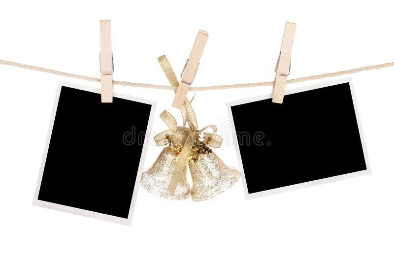 空白的照片框架和垂悬在clotheslin的圣诞节装饰 免版税库存图片