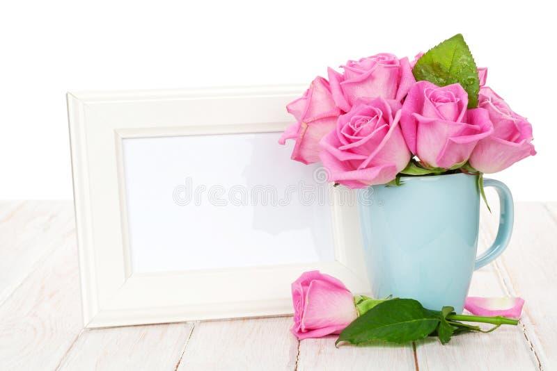 空白的照片框架和桃红色玫瑰花束在茶杯 免版税图库摄影
