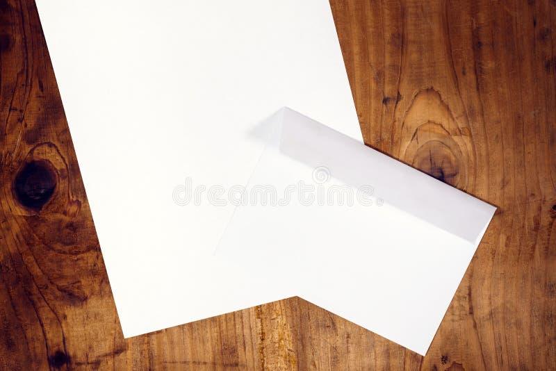 空白的白色信封和纸在木书桌上 免版税库存照片