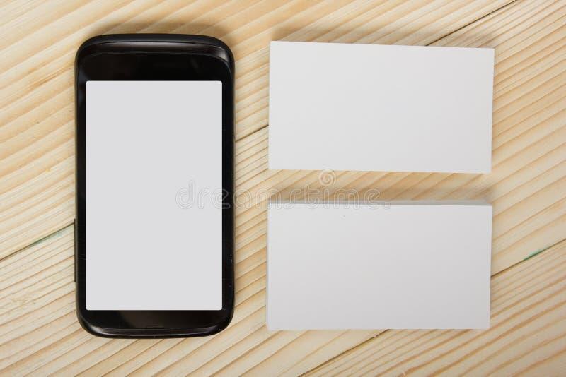 空白的白色名片和智能手机在木背景 库存图片