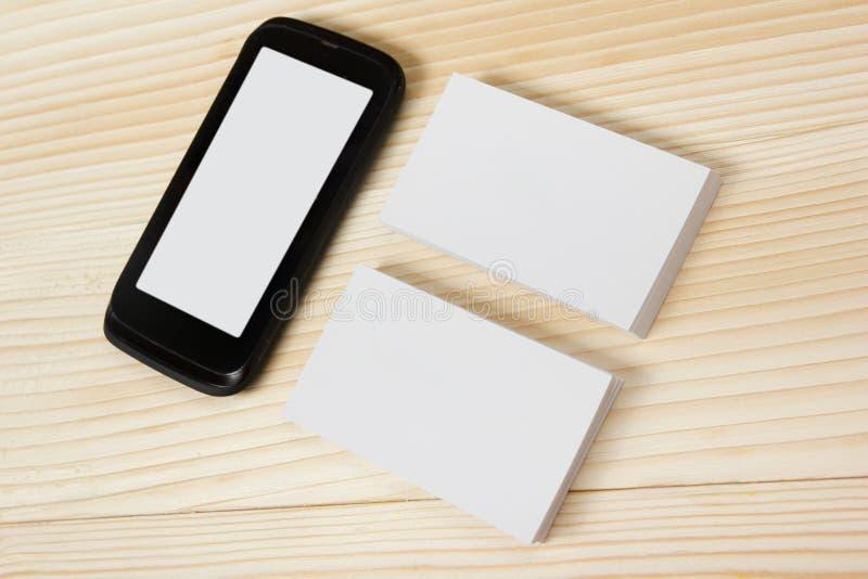 空白的白色名片和智能手机在木背景 免版税库存图片