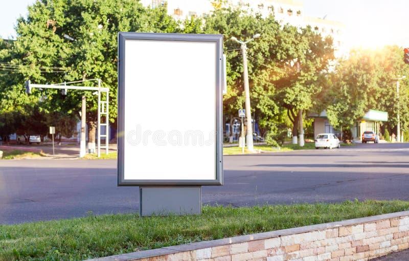 空白的白色嘲笑在一个公共汽车站的垂直的灯箱在美好的天气和阳光 免版税库存照片