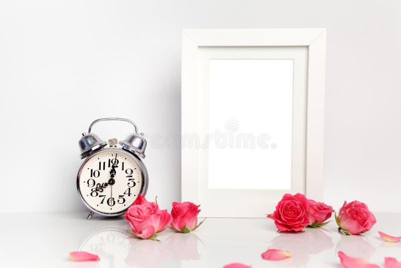 空白的白色框架、桃红色玫瑰和闹钟 嘲笑 免版税图库摄影