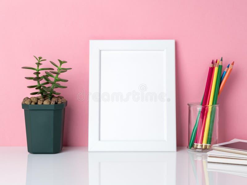 空白的白色框架,在瓶子,在一张白色桌上的植物仙人掌的蜡笔 免版税库存照片