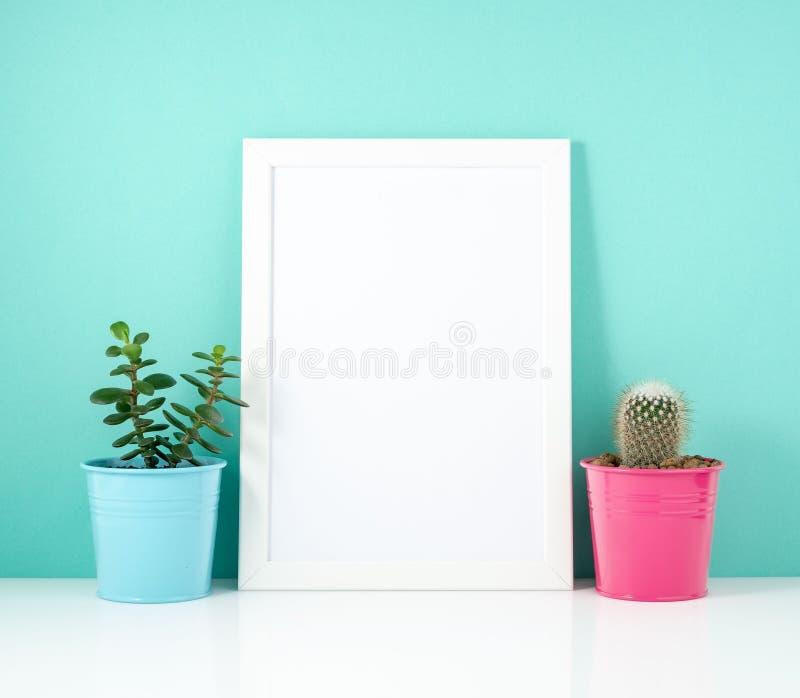 空白的白色框架,在白色桌上的植物仙人掌对蓝色墙壁 与拷贝空间的大模型 免版税库存照片