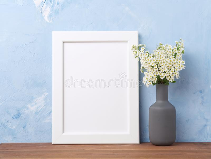 空白的白色框架,在vaze的花在棕色木桌上对有拷贝空间的淡色蓝色混凝土墙 嘲笑 免版税库存图片