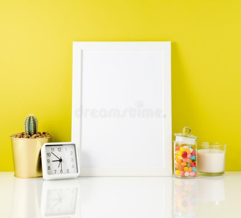 空白的白色框架,时钟,多汁植物,在一张白色桌上的糖果对yelloow墙壁 与拷贝空间的大模型 库存照片