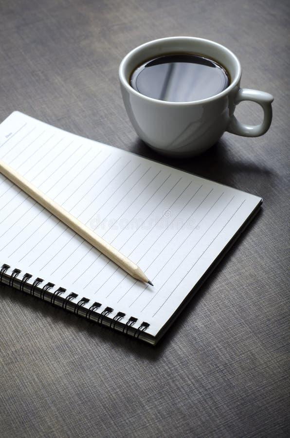 空白的白色笔记本、笔和咖啡在书桌上的 免版税库存照片