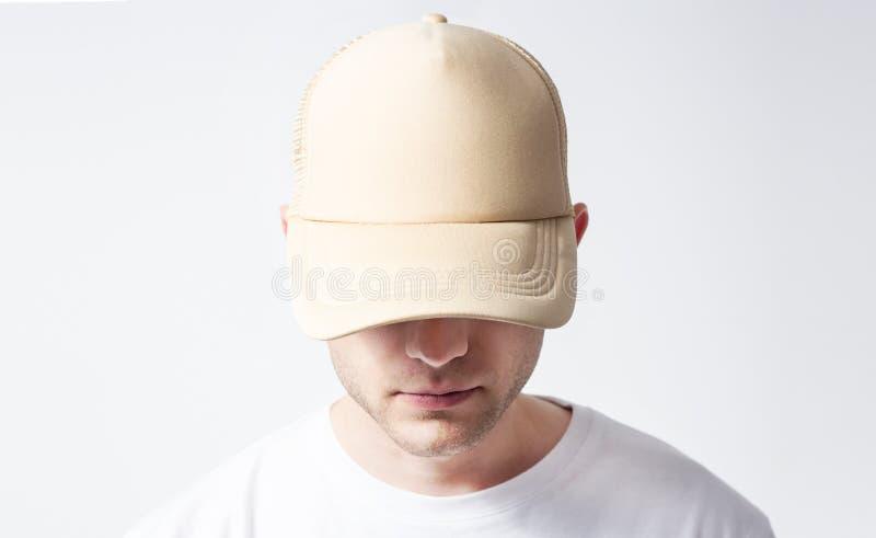 空白的白色,米黄棒球帽的人在白色背景 免版税库存照片