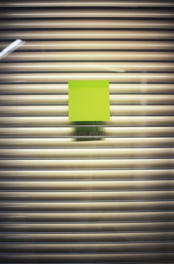 空白的稠粘的笔记的图象关于办公室玻璃墙的有百叶窗的 库存照片