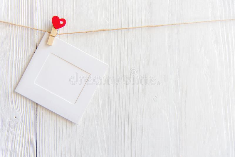 空白的立即照片垂悬在晒衣绳的框架和红色心脏 免版税库存图片