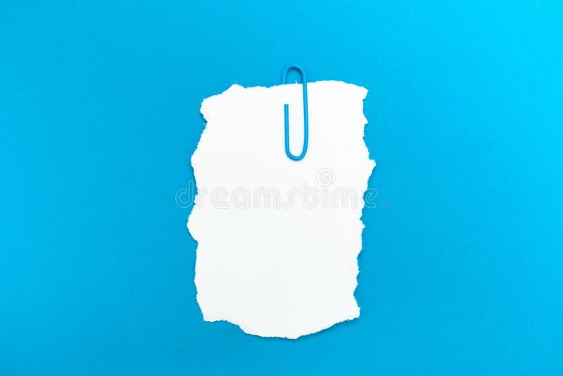 空白的笔记、一个提示与一个被撕毁的边缘和一个纸夹在蓝色背景 免版税库存图片