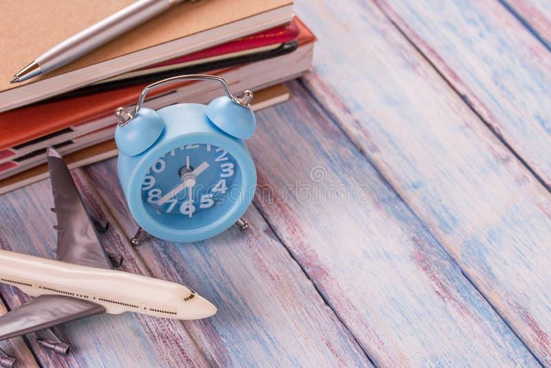 空白的笔记本、飞机玩具、笔和闹钟在办公桌w上 库存照片
