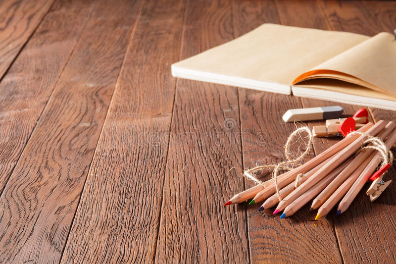 空白的笔记本和五颜六色的铅笔在木桌上 橡皮擦和木别针 免版税库存照片