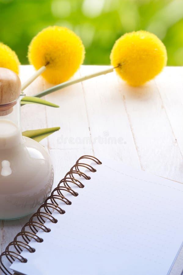 空白的笔记本和牛奶瓶在木桌上与绿色摘要 库存图片