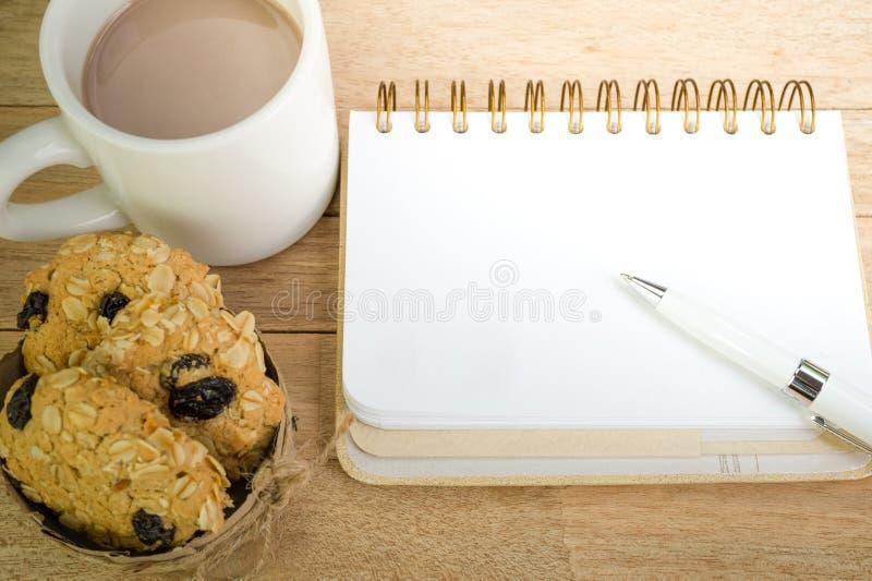 空白的笔记本用在木背景的咖啡和燕麦曲奇饼 免版税图库摄影