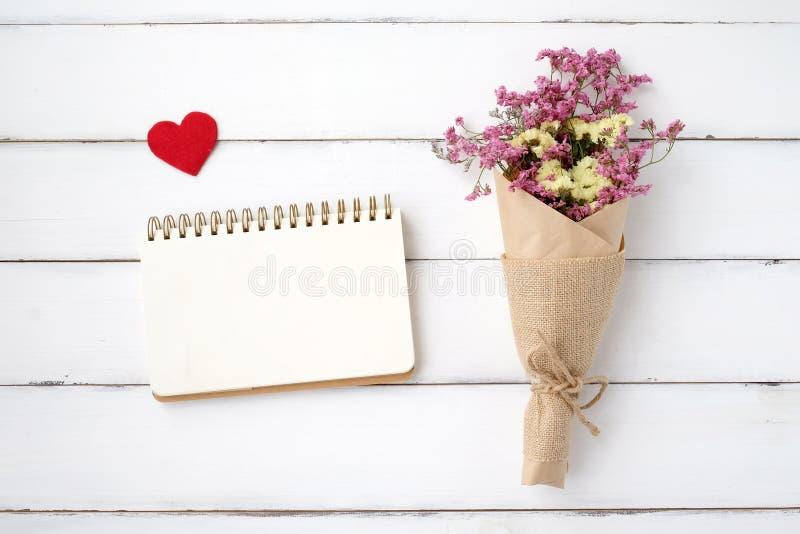空白的笔记本纸、织品心脏形状和花花束 库存照片