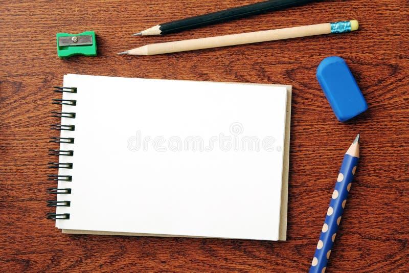 空白的笔记本纸和铅笔在木背景与拷贝s 库存图片