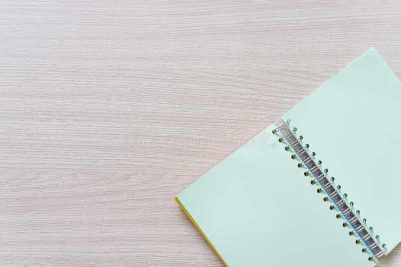 空白的笔记本顶视图在木背景的与拷贝空间 免版税库存图片