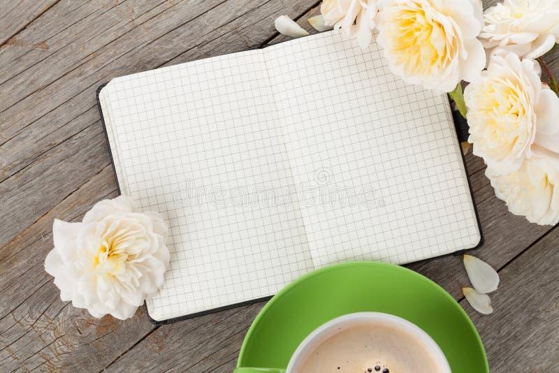 空白的笔记薄、咖啡杯和白色玫瑰开花 库存图片