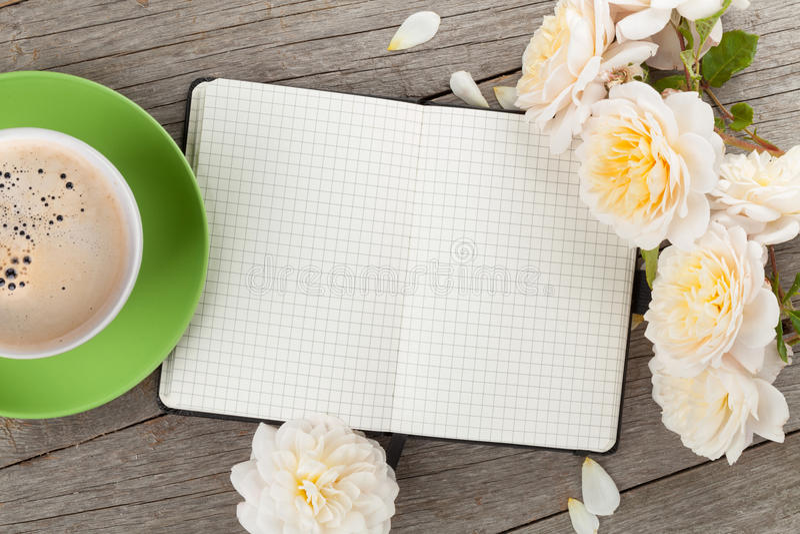 空白的笔记薄、咖啡杯和白色玫瑰开花 免版税库存图片