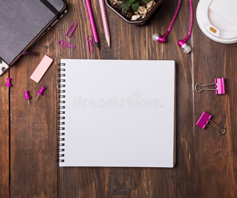 空白的笔记薄和桃红色颜色文具在木桌上 免版税库存照片