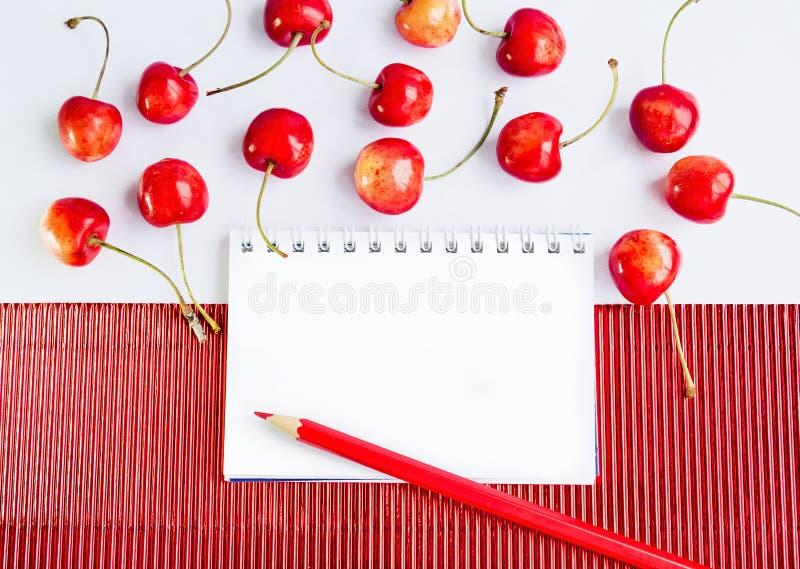 空白的笔记薄铅笔和樱桃 库存图片