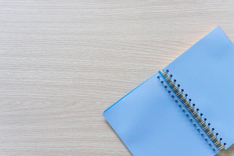 空白的蓝色笔记本顶视图在木背景的与拷贝空间 免版税库存图片