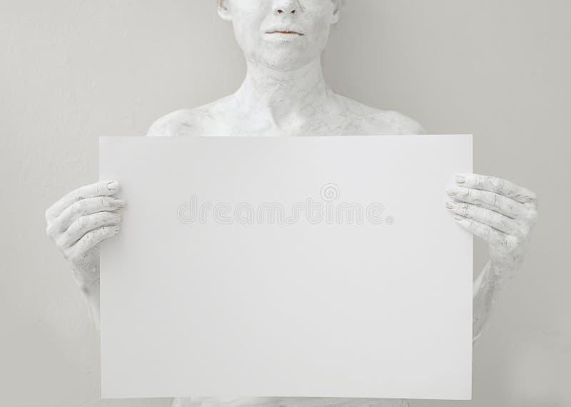 空白的设计海报模板 用白色油漆盖的妇女拿着纸 库存照片