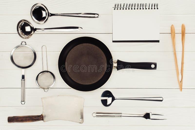 空白的课本、煎锅、屠户轴和厨房器物顶视图在白色木 库存照片