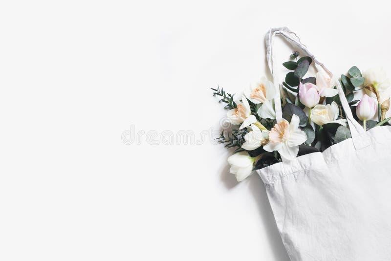 空白的购物的帆布大手提袋大模型特写镜头与桃红色郁金香、黄水仙在白色隔绝的花和玉树的 免版税库存照片