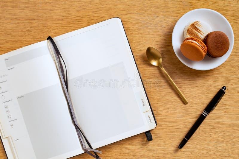 空白的食谱笔记本和一支笔用棕色和白色法国蛋白杏仁饼干在一块板材有一把金黄匙子的,橡木背景 免版税图库摄影