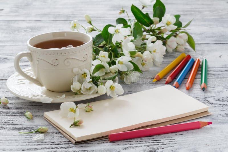 空白的贺卡和杯子与开花的樱桃分支的绿色花茶在白色土气木背景的 免版税库存图片
