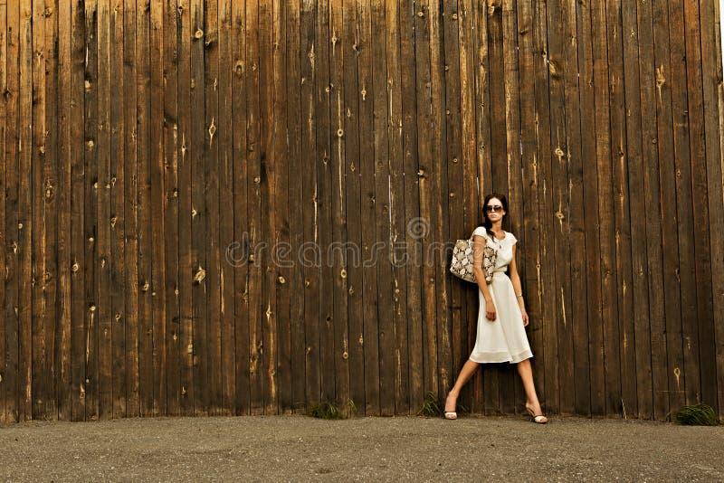 空白礼服的美丽的女孩对墙壁 免版税库存照片