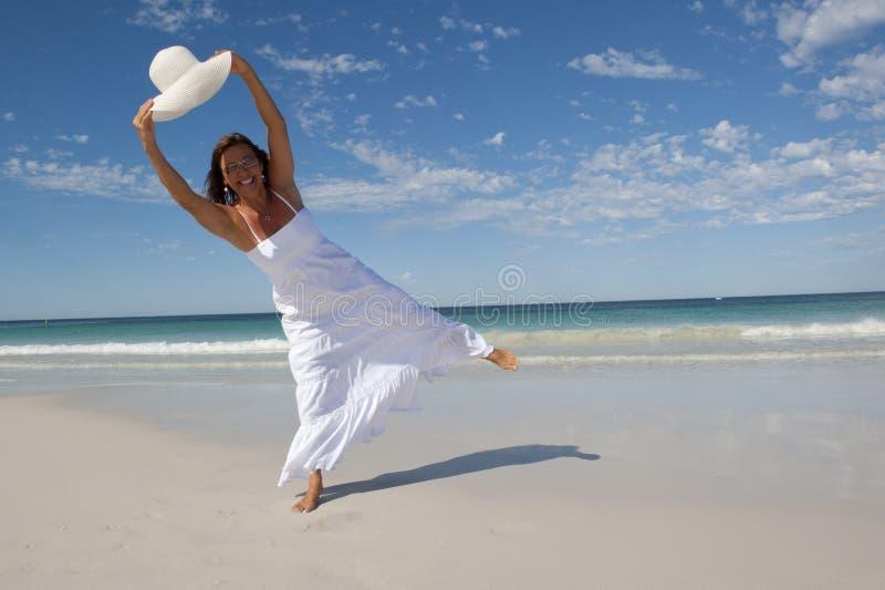 空白礼服的美丽的妇女在海滩 免版税库存图片