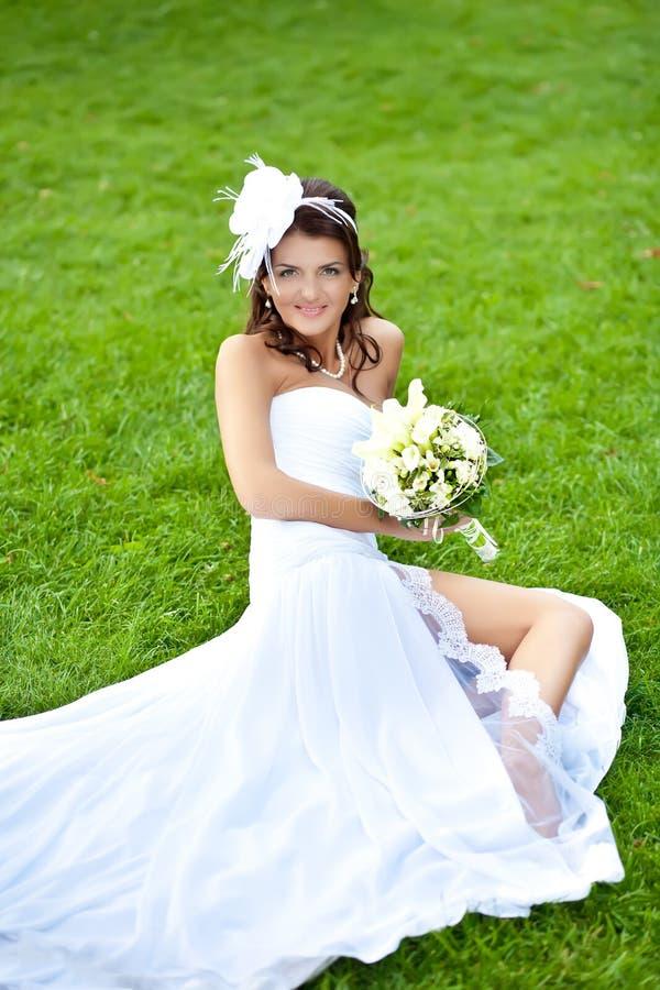 空白礼服选址的愉快的新娘在绿草 库存照片