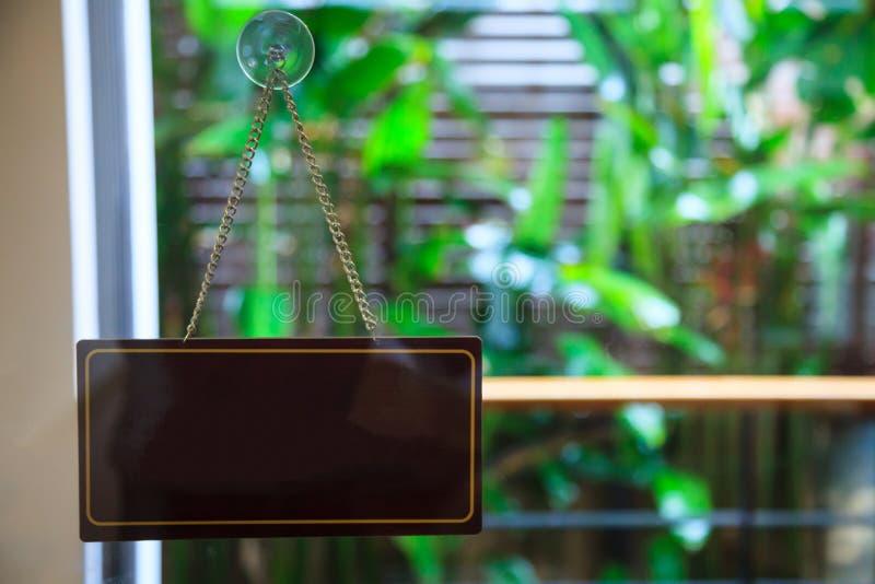 空白空的木拉门吊挂装置垂悬的横幅或牌与吸杯子真空墙壁勾子,夹住光滑的玻璃的吮吸者 免版税库存图片