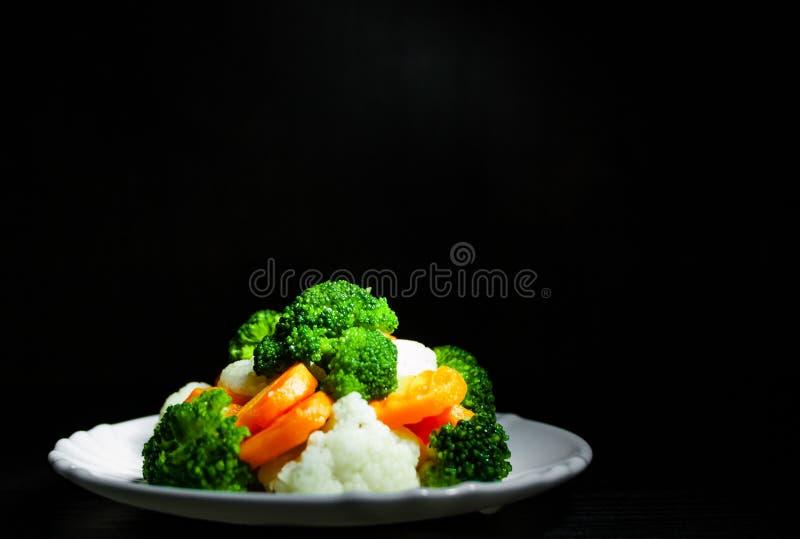 空白背景新鲜的庭院混杂的蔬菜 花椰菜、硬花甘蓝和红萝卜在板材在老黑暗的木背景 库存图片