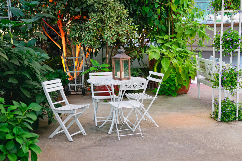 空白表和椅子在美丽的庭院里。 库存图片