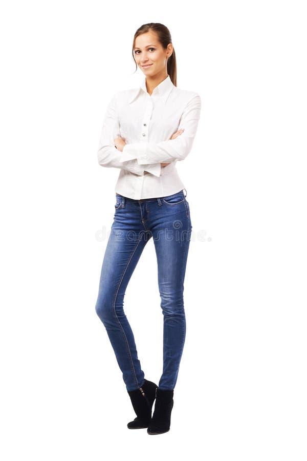 空白衬衣和蓝色牛仔裤的可爱的妇女 免版税库存照片