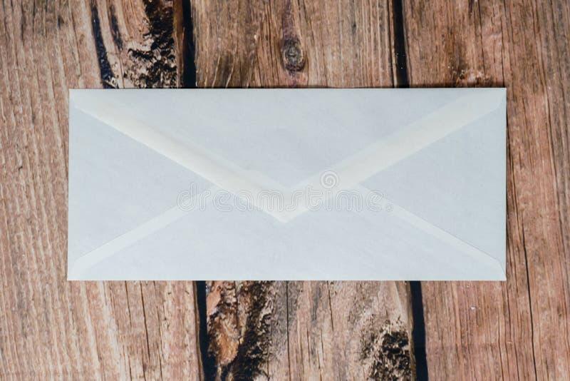 空白邮寄的一个传统白色信封在黑暗的木背景 库存照片