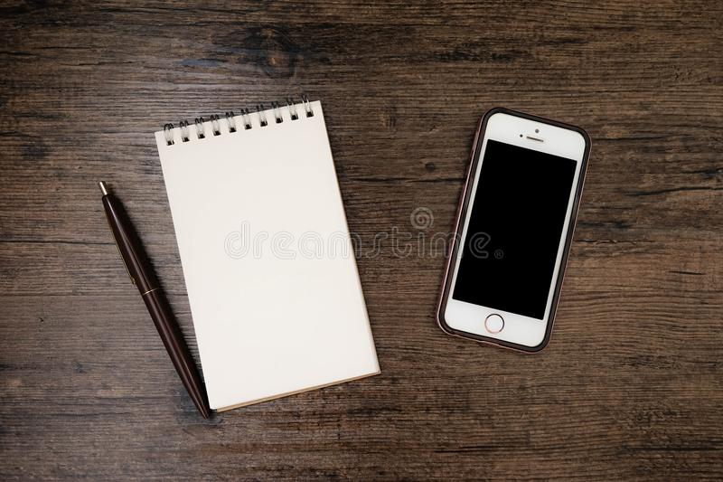 空白页笔记本和在木桌上的手机的顶视图图象有笔的 免版税库存照片