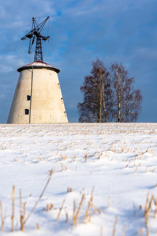 空的乡下风景在与报道地面的雪的晴朗的冬日用大被放弃的风车在背景中 库存图片