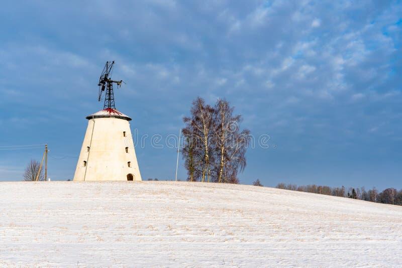 空的乡下风景在与报道地面的雪的晴朗的冬日用大被放弃的风车在背景中 库存照片