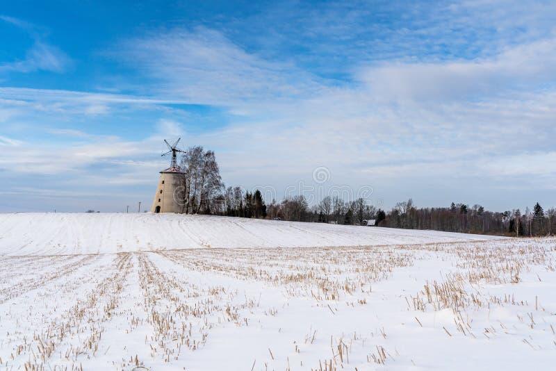 空的乡下风景在与报道地面的雪的晴朗的冬日用大被放弃的风车在背景中 免版税库存照片